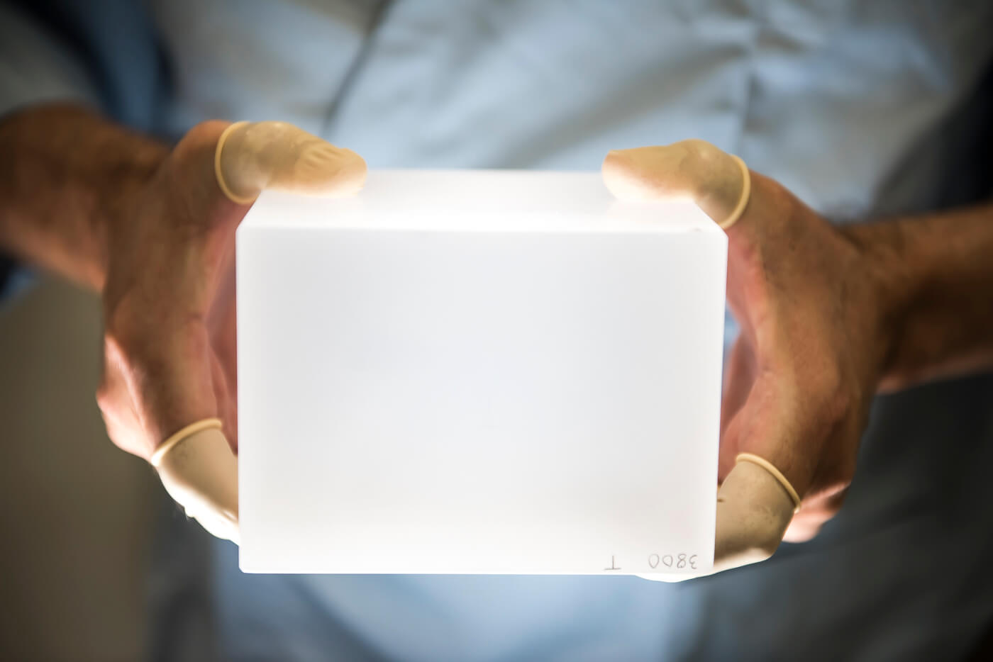 Lab tech holding optical glass sample.